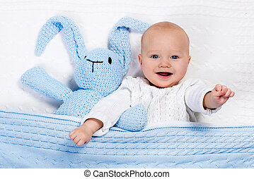 Baby boy playing with bunny toy in bed - Funny little baby...