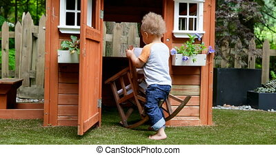 Baby boy playing with chair in play house at backyard 4k