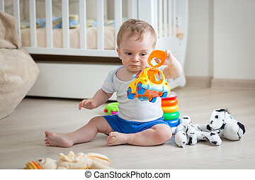 Baby boy playing with colorful toy car on floor at living room