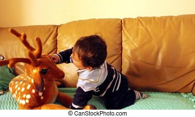 Baby boy playing with dear soft toy