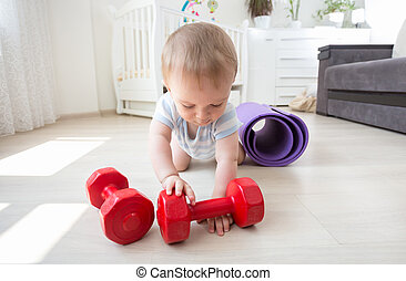 Baby boy playing with dumbbells on floor at home