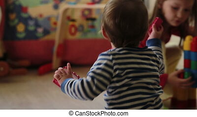baby boy playing with his sister in the nursery