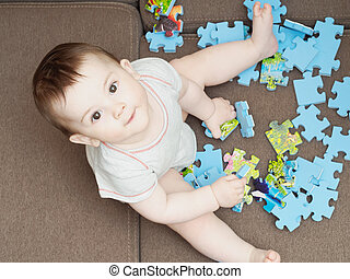 Baby boy playing with puzzle pieces on sofa in the living room at home