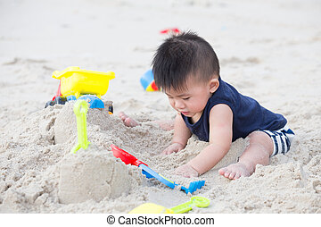 Baby boy playing with sand on tropical beach