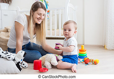 Baby boy playing with toy cellphone on floor at living room