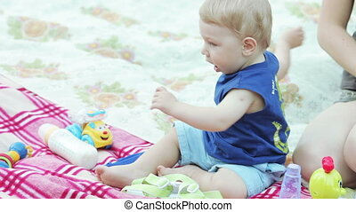 Baby boy playing with toy in nature