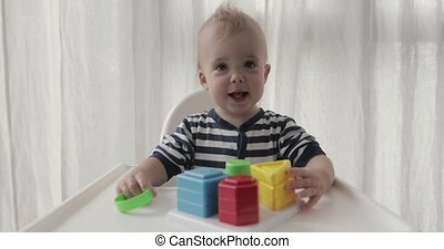 Baby boy plays educational toy sitting high chair - Close up...