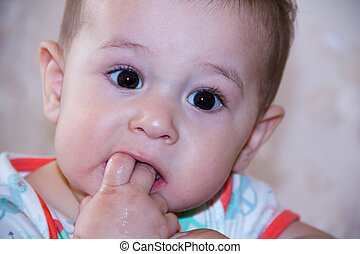 Baby boy plays with fingers in mouth and happy facial expression. Portrait of a crawling smiling. Teething infant playing. Newborn child at home. The scratching his teeth.