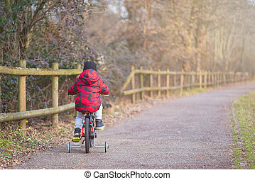 Baby boy riding his bicycle on the cycle path at sunset