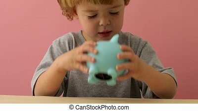 Baby boy shakes his piggy bank