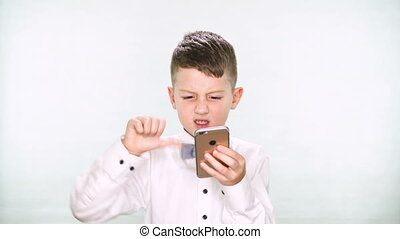 Baby boy shows thumbs down and playing with a tablet or smartphone on white background