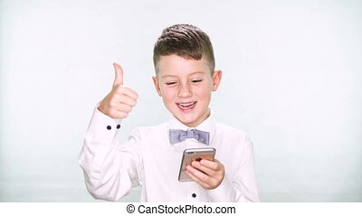 Baby boy shows thumbs up and playing with a tablet or smartphone on white background