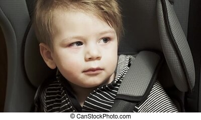 Baby boy sits on a child seat in the car
