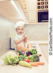 Baby boy sitting among vegetables in the kitchen and prepares for cooking