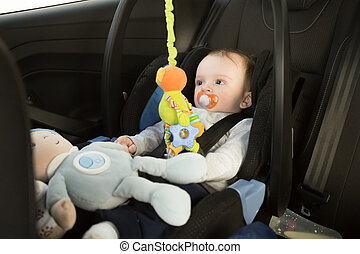 Baby boy sitting in car seat and playing with toys
