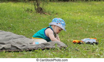 Baby boy sitting in the meadow, trying to eat grass