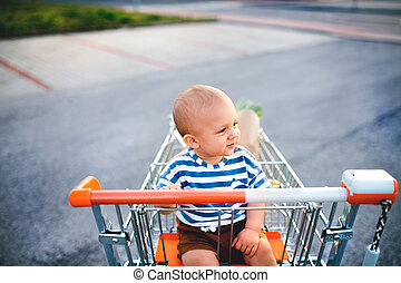 Baby boy sitting in the shopping trolley outside.