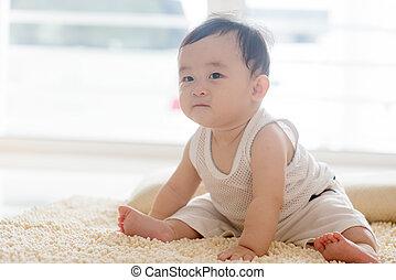 Baby boy sitting on carpet.