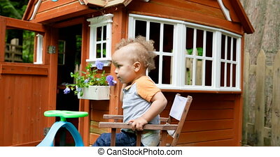 Baby boy sitting on chair near play house at backyard 4k