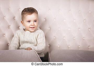 baby boy sitting on elegant sofa