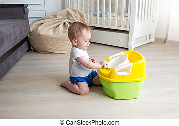Baby boy sitting on floor and looking at chamber pot