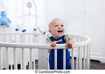 Baby boy standing in bed - Cute laughing baby standing in a ...