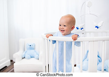 Baby boy standing in bed in white nursery - Funny little...