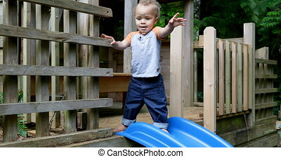 Baby boy standing near slide in play house at backyard 4k