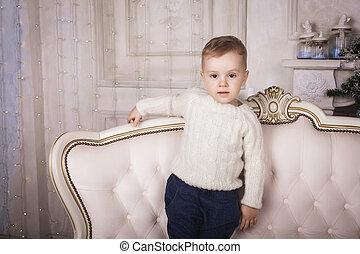 baby boy standing on elegant sofa