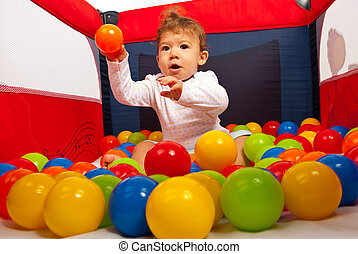 Baby boy throw the ball - Baby boy sitting in playpen with...