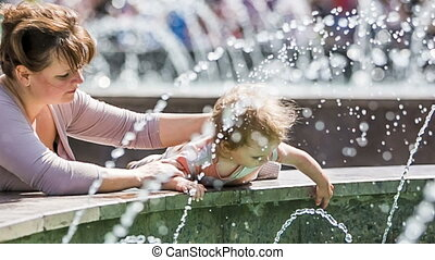 Baby Boy Touching Water In The Fountain