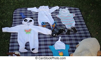 Baby boy toys and clothes on rug in park
