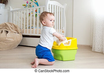 Baby boy trying to sit on chamber pot at bedroom