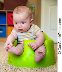Baby boy using training Bumbo seat