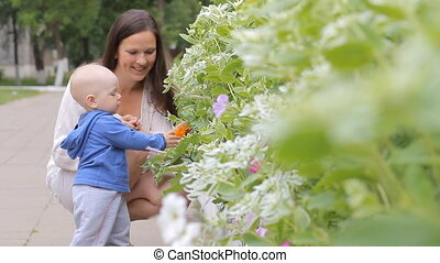 Baby boy walking in the park with mom's support near flowers