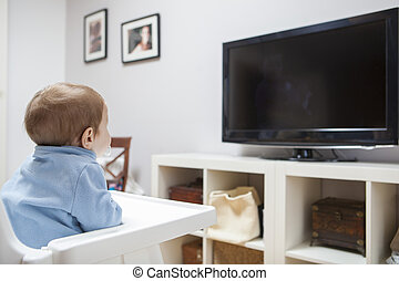 Baby boy watching television in living room - Baby boy...