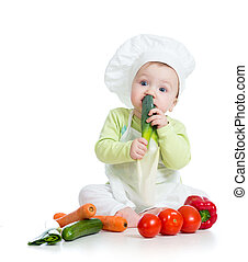 baby boy wearing a chef hat with healthy  food vegetables