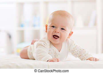 Baby boy wearing white clothes in sunny nursery. Newborn child relaxing in bed.