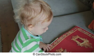 Baby boy with book point to camera