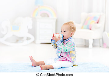 Baby boy with bottle drinking milk or formula