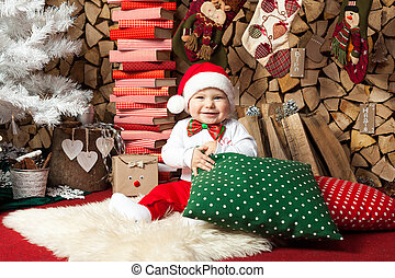 Baby boy with cushions at Christmas tree