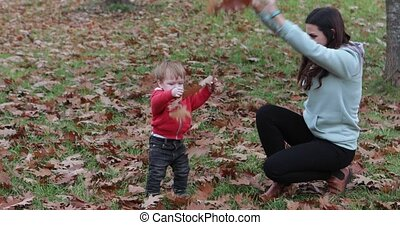 Baby boy with his mother throw leaves