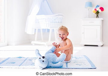 Baby boy with milk bottle in sunny nursery - Cute blond...