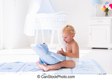 Baby boy with milk bottle in sunny nursery