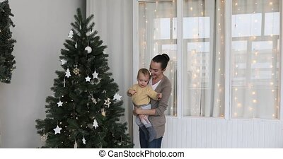 Baby boy with mother decorates the Christmas tree