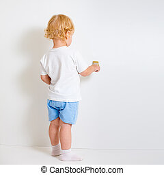 Baby boy with paint brush rear view standing near blank white wall