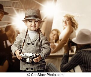 Baby boy with retro camera over photo shoot background.