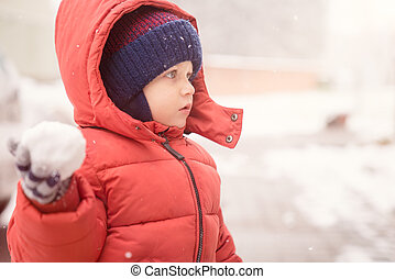 Baby boy with snowball while snowing