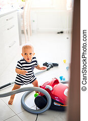 Baby boy with the hoover in the kitchen.