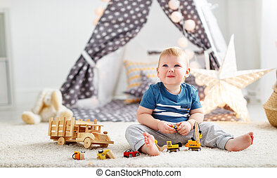 baby boy with toy cars in   children's playroom